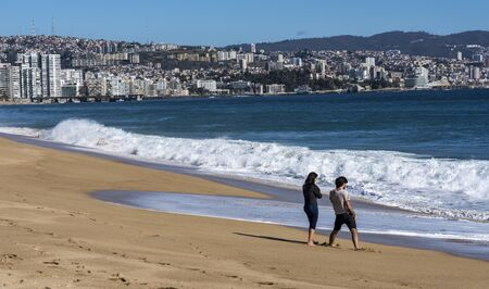 Valparaiso, Chile - 2019-07-30 - Two people walk along the beach with the skyline in the background.