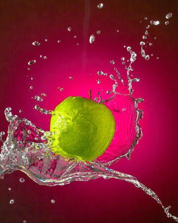 Water Splashes on Green Apple wet fruit throw Stock Photo