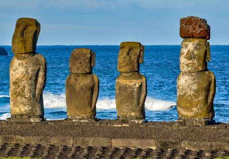 Moai on Easter Island with red topknot hats at Anakena Ahu. Archivio Fotografico