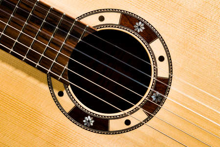 Closeup of the rosette sound hole of an acoustic guitar