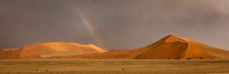 Rainbow shines over a sand dune in the desert in Namibia Stock fotó