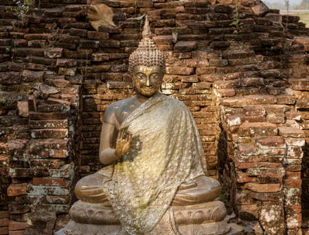 Sitting Stone Buddha in an Ancient Brick Alcove.