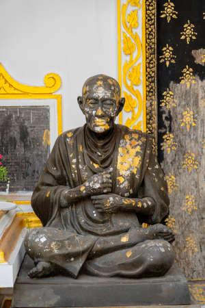 Statue of Sitting Monk Splattered With Paint. Foto de archivo