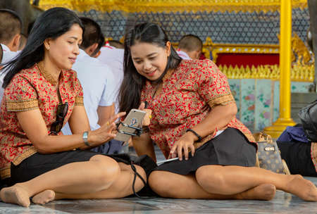 Two women using a cell phone while sitting on a floor in Bangkok, Thailand
