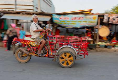 Sukhothai, Tahiland - 2019-03-06 - Old Man Drives His Three Wheeled Motor Cart Through Market. 新聞圖片