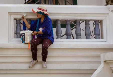 Woman sits on ledge painting a balcony at the Grand Palace in Bangkok, Thailand