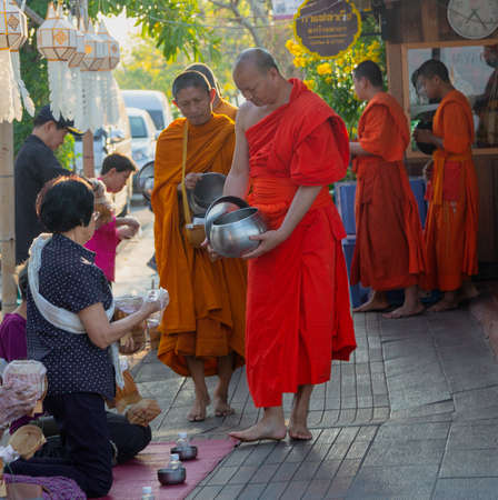 Lampeng, Tahiland - 2019-03-07 - Line of Monks Receive Gifts of Food From Worshippers Along Street. Editorial