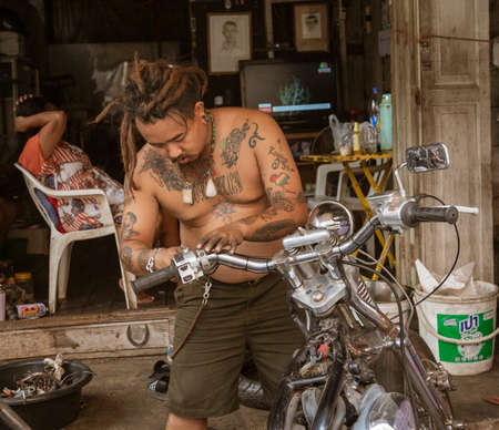 Lampeng, Tahiland - 2019-03-07 - Man With Many Tattoos Repairs His Motorcycle.
