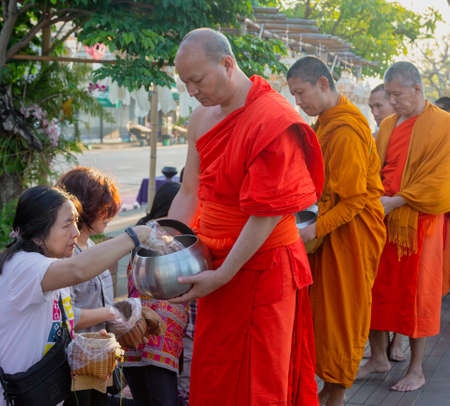 Lampeng, Tahiland - 2019-03-07 - Line of Monks Receive Gifts of Food From Worshippers Along Street. Redactioneel