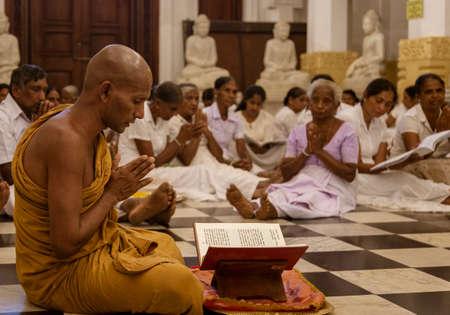 Kandy, Sri Lanka - 09-03-24 - Monk Leads Worshippers in Prayer in Temple. Redactioneel