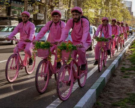 Tehran, Iran - 2019-04-03 - Men ride bicycles in pink to promote new bike rental company.