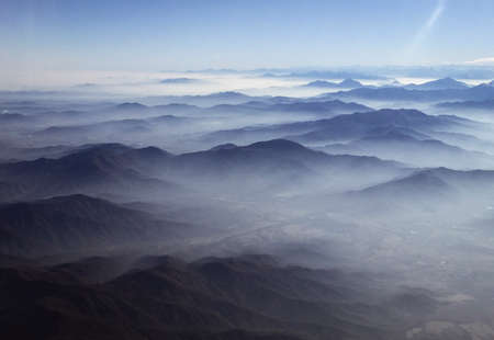 Clouds linger over hills stretching into distance, as photographed from airplane window flying over Chile.