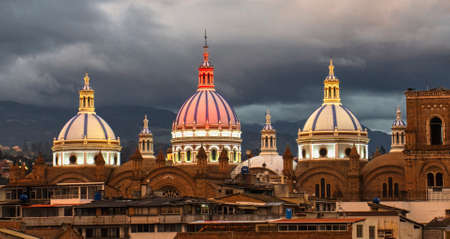 New Cathedral Domes in Cuenca, Ecuador are illuminated in the city flag colors for Independence Day, shown at dusk.