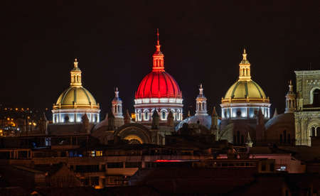 New Cathedral Domes in Cuenca, Ecuador are illuminated in the city flag colors for Independence Day, shown at night.