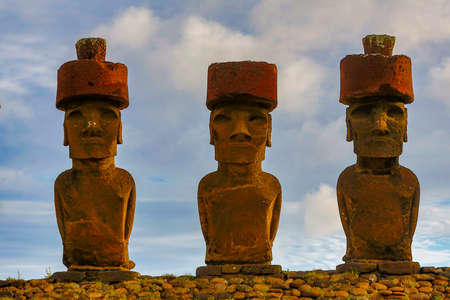 Moai on Easter Island with red topknot hats at Anakena Ahu. Banque d'images