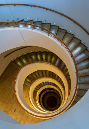 Spiral Staircase Leads Down Several Floors With Dramatic Lighting. Banque d'images