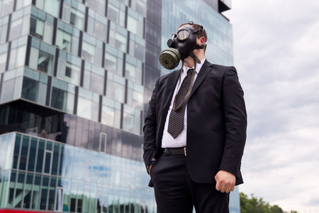 Businessman in the city wearing a gas mask on the face.
