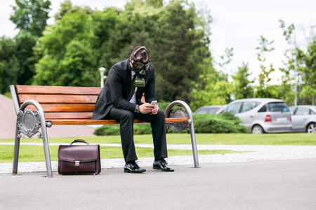 Businessman sitting on a banch wearing a gas mask looking to the phone
