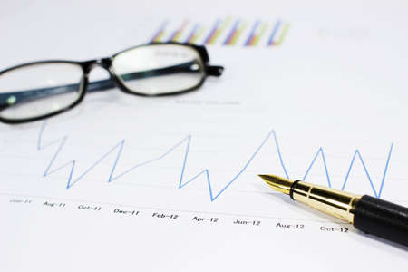 sales volume charts on the table with  pen