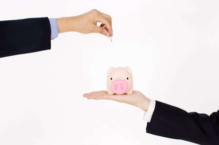mens hand putting coin into a piggy bank  Stock Photo