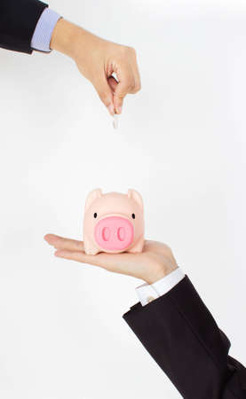 men hand putting coin into a piggy bank photo