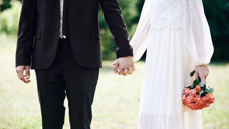 Liefhebbers hand in hand in zomerpark. Trouwdag met mooie klassieke stijl. Mooie bruid in witte jurk met rozenboeket. Stockfoto