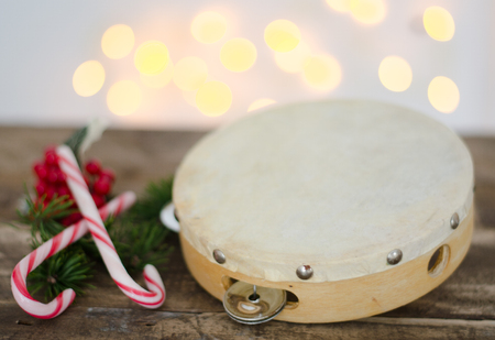 tambourine: Tambourine with Christmas candy on wooden table and background lighting Stock Photo