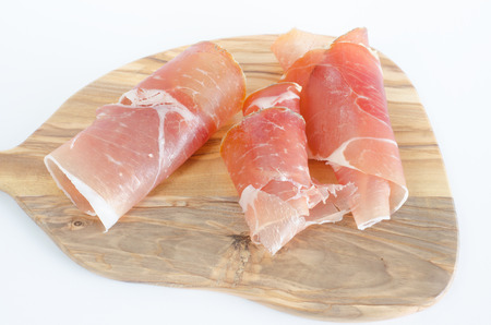 Ham on olive wood board and white background. Stock Photo