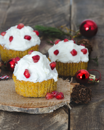 pinecones: Cream cupcake and pomegranate with Christmas decoration, on rustic wooden background.
