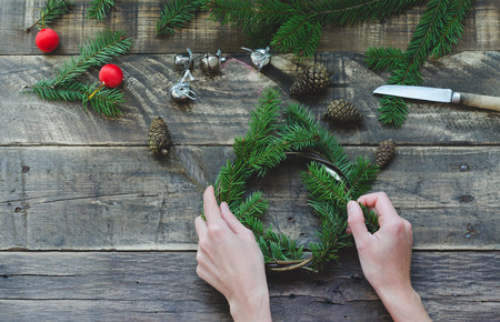 Elaboration of pine wreath with the hands of a person and christmas decoration on rustic wooden background. Cenital plane. Stock Photo