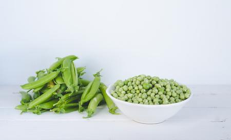 Peas in white bowl on white background.