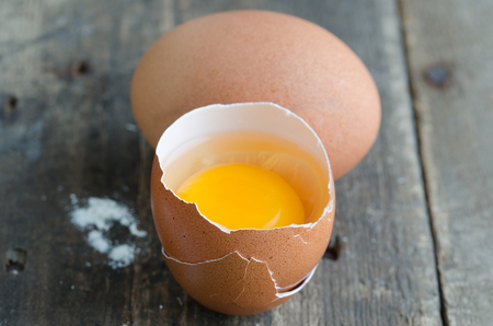 Broken egg on rustic wood bottom.