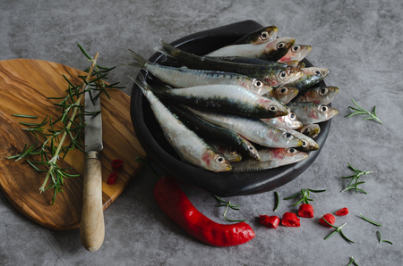 Sardines in black ceramic bowl with chilli peppers on marble background.