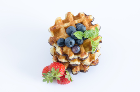 Waffles with red berries on white background. Top view.