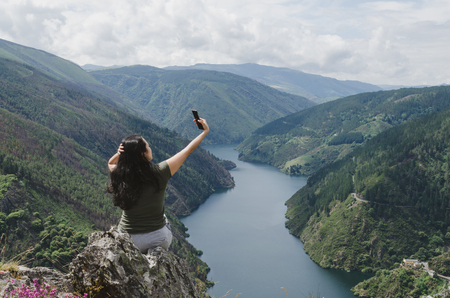 Woman taking selfie in a mountain landscape with river.