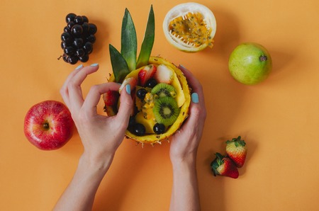 Assorted fruits with woman's hand on rustic wooden background. Flat lay. Space to write.