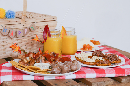 Food and drinks picnic on rustic wooden table with checkered tablecloth.