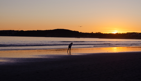 Woman looking at the sand on the beach of La Lanzada, O Grove, Pontevedra, Galicia, Spain. No people. Imagens