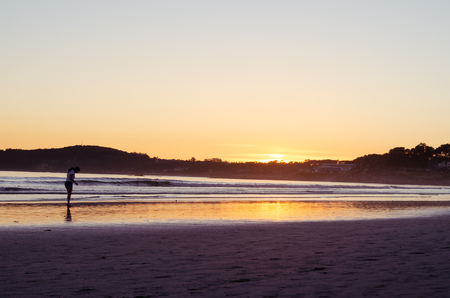 Woman looking at the sand at sunset on the beach of La Lanzada, O Grove, Pontevedra, Galicia, Spain. No people.