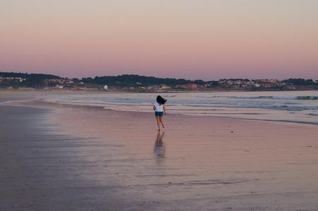 Woman running at sunset on the beach of La Lanzada, O Grove, Pontevedra, Galicia, Spain. No people. Imagens