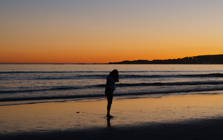 Woman looking at the sand at sunset from the beach of La Lanzada, O Grove, Pontevedra, Galicia, Spain Imagens