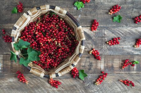Currants in wooden basket on dark wooden background. Flat lay. Banque d'images - 132268538