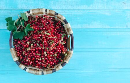Currants in wooden basket on blue wooden background. Copy space Flat lay. Banque d'images - 132268540