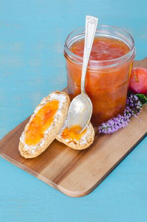 Homemade plum jam in glass jar on wooden table and blue background.
