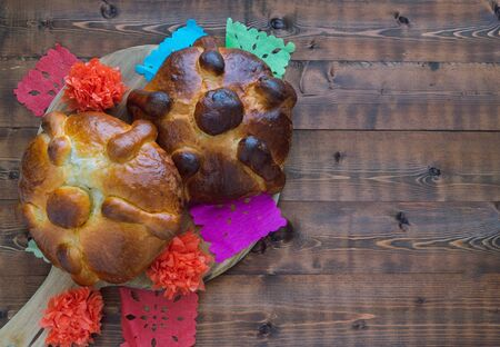 Two pieces of bread of the dead on dark wooden background. Copy space. Mexican party.