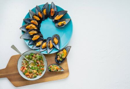 Steamed mussels with onion, tomato and cilantro vinaigrette on white background and kitchen board. Copy space. Top view. Reklamní fotografie