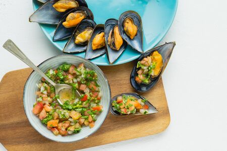 Steamed mussels with onion, tomato and cilantro vinaigrette on white background and kitchen board. Top view.