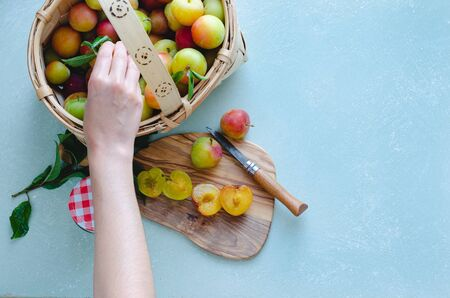 Basket with plums, hand grabbing plums. Fresh fruit. Plums cut.