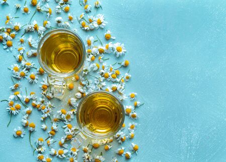 Cup of chamomile with flowers on blue background. Copy space Flat lay.