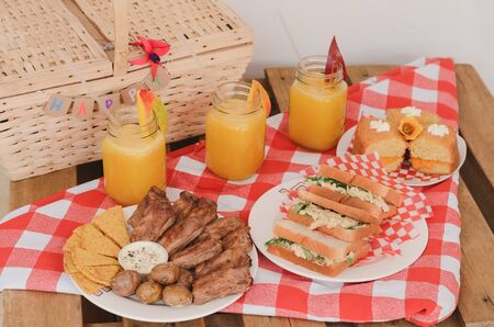 Picnic lunch. Baked ribs, sanwich, mango juice and cake. Stock fotó